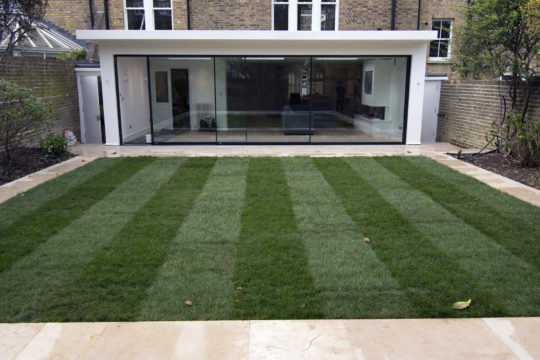Full width glass extension leading onto terraced garden landscaping